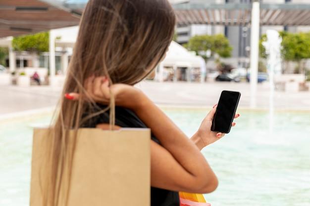 Tylna widok kobieta patrzeje smartphone
