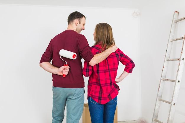 Tylna widok para patrzeje malującą ścianę