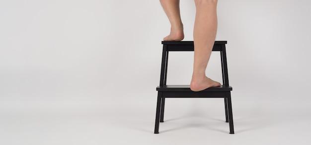 Tylne nogi i bose stopy na drewnianym stołku lub drabinie na białym tle.