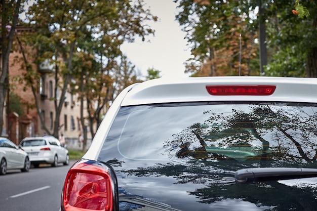 Tylne okno białego samochodu zaparkowanego na ulicy w słoneczny letni dzień, widok z tyłu. makieta do naklejek lub kalkomanii