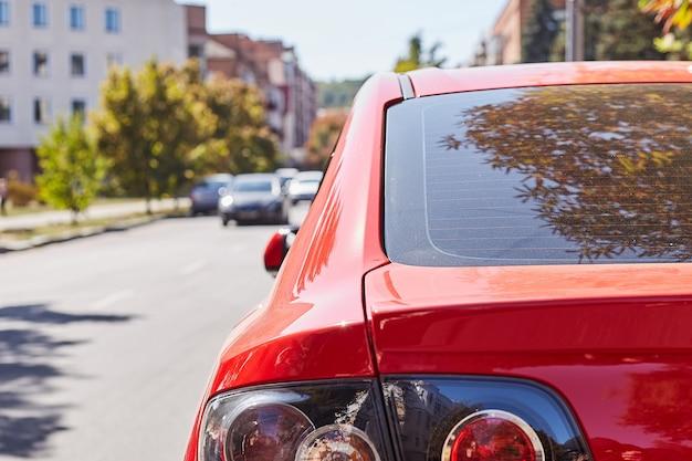 Tylne okno czerwonego samochodu zaparkowanego na ulicy w słoneczny letni dzień, widok z tyłu. makieta do naklejek lub kalkomanii