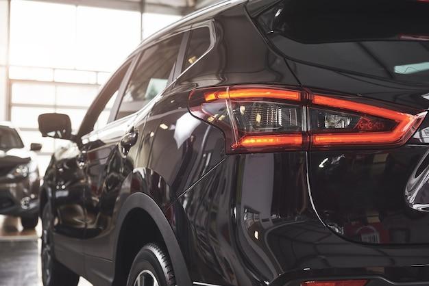 Tylne reflektory czarnego luksusowego samochodu.