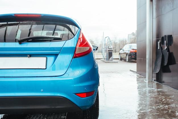 Tylne światło niebieskiego hatchbacka stojącego na myjni samochodowej