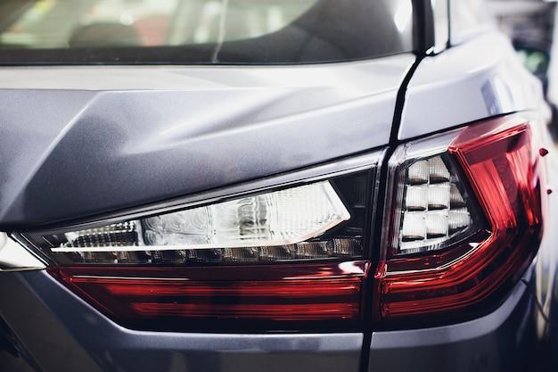 Tylne światło z błyszczącymi refleksami, auto czarne ciało