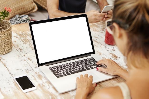 Tylne ujęcie studentki uczącej się online na laptopie przed wykładami.