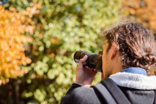 Tylne zdjęcie fotografa fotografowania jesiennego parku. koncepcja zobrazowania sezonu jesiennego na zdjęciach