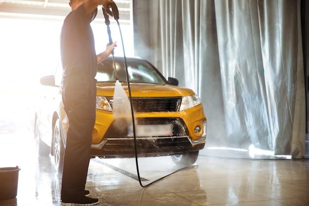 Tylne zdjęcie pracownika myjni samochodowej ze specjalnym wężem w dłoniach podczas mycia crossovera