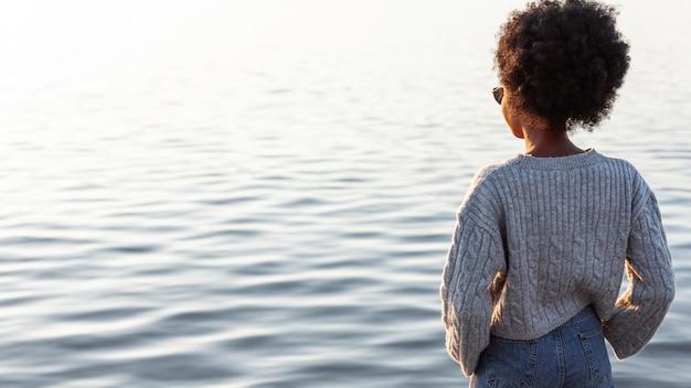 Tylnego widoku afrykańska kobieta patrzeje wodę