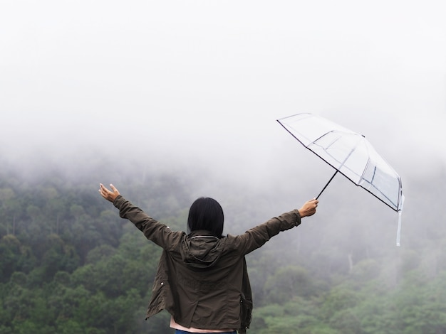 Tylnego widoku szczęśliwej kobiety chwyta turystyczny parasol nad zielonym lasu tropikalnego tłem.