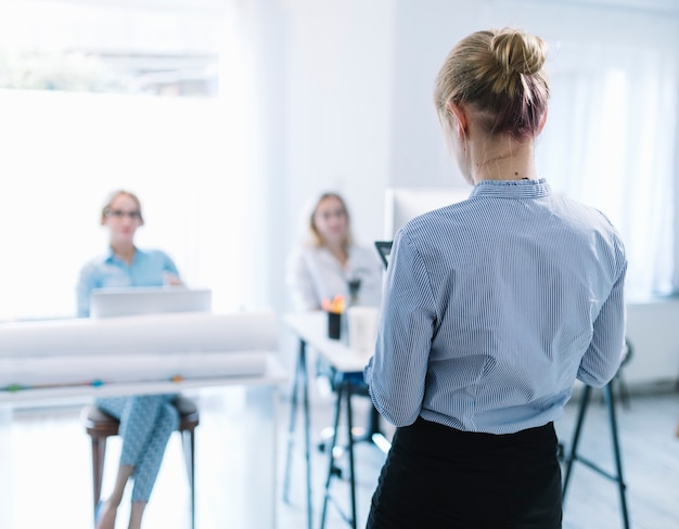 Tylni widok bizneswoman daje prezentaci w spotkaniu