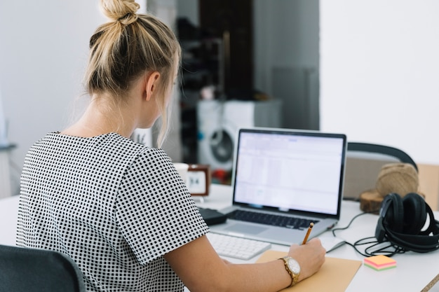Tylni widok bizneswomanu writing notatki nad brown papierem z laptopem na biurku