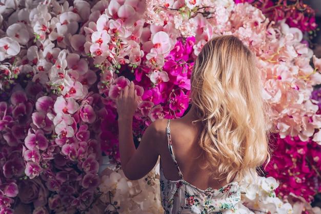 Tylni widok blondynki młoda kobieta patrzeje storczykowych kwiaty
