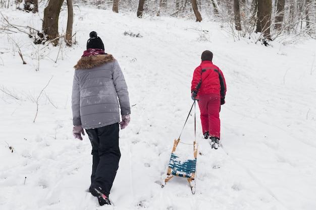 Tylni widok chłopiec i dziewczyny odprowadzenie z pustymi saneczki w śnieżnym lesie