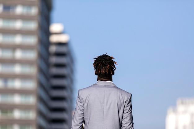 Tylni widok czarnego afrykanina młody człowiek patrzeje daleko od przeciw niebieskiemu niebu w mieście