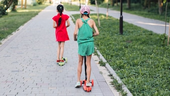 Tylni widok dwa dziewczyny jedzie pchnięcie hulajnoga w parku
