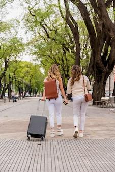 Tylni widok dwa młodej kobiety chodzi w parku z bagaż torbą