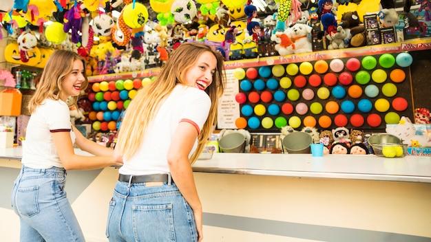 Tylni widok dwa szczęśliwego żeńskiego przyjaciela stoi przed zabawka sklepem