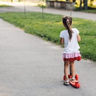 Tylni widok dziewczyny jazdy pchnięcia hulajnoga przy ulicą