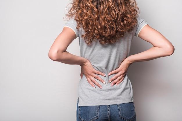 Tylni widok kobieta ma backache przeciw popielatemu tłu