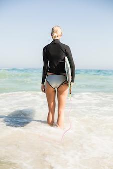 Tylni widok kobieta z surfboard pozycją na plaży