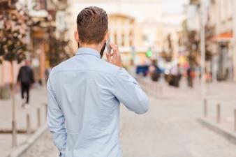 Tylni widok mężczyzna opowiada na smartphone przy outdoors