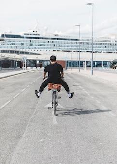 Tylni widok mężczyzna jedzie bicykl z jego nogą szeroko rozpościerać o droga