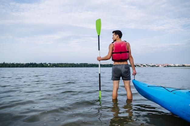 Tylni widok mężczyzna mienia wiosła i kajaka pozycja w jeziorze