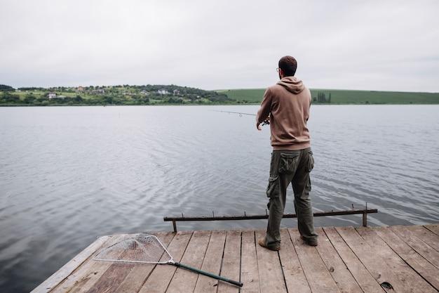 Tylni widok mężczyzna pozycja na mola połowie w jeziorze