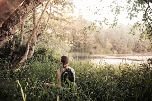 Tylni widok mężczyzna pozycja w trawie patrzeje jezioro