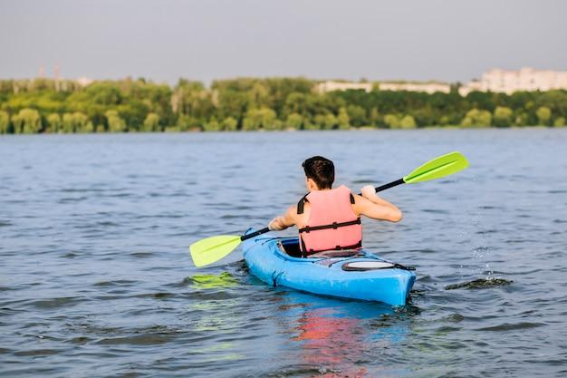 Tylni widok mężczyzna używa paddle dla kayaking