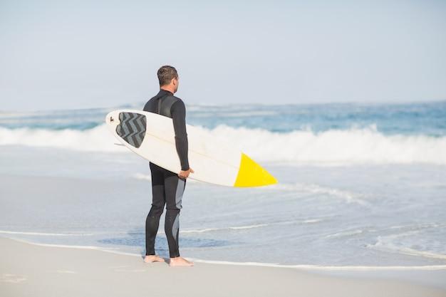 Tylni widok mężczyzna z surfboard pozycją na plaży