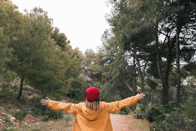 Tylni widok młoda kobieta out rozciąga jego rękę w lesie