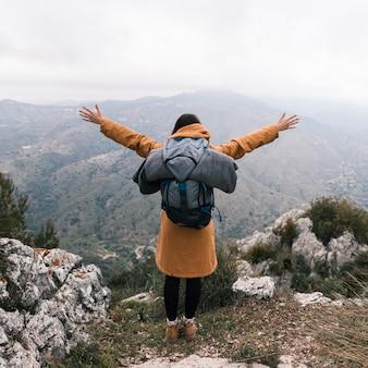 Tylni widok młoda kobieta out rozciąga jego rękę z plecakiem patrzeje widok