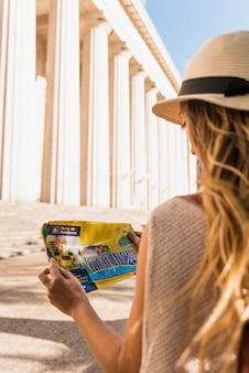 Tylni widok młody żeński turysta patrzeje mapę