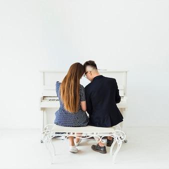 Tylni widok potomstwa dobiera się obsiadanie przed pianinem przeciw biel ścianie