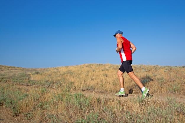 Tylni widok sportowy biegacza bieg na halnym śladzie na niebieskiego nieba tle