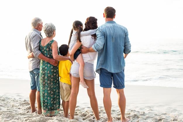 Tylni widok szczęśliwa rodzina pozuje przy plażą