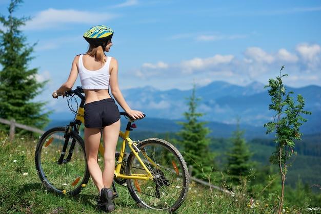 Tylni widoku młoda atrakcyjna żeńskiej atlety pozycja na wiejskim śladzie z żółtym bicyklem, cieszący się dolinnego widok i mgłowe góry na tle w ranku.