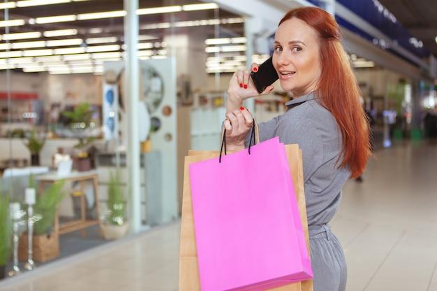 Tylni widoku strzał piękna kobieta patrzeje kamera, opowiada na jej telefonie podczas gdy robiący zakupy przy centrum handlowym. konsumpcjonizm, koncepcja miejskiego stylu życia