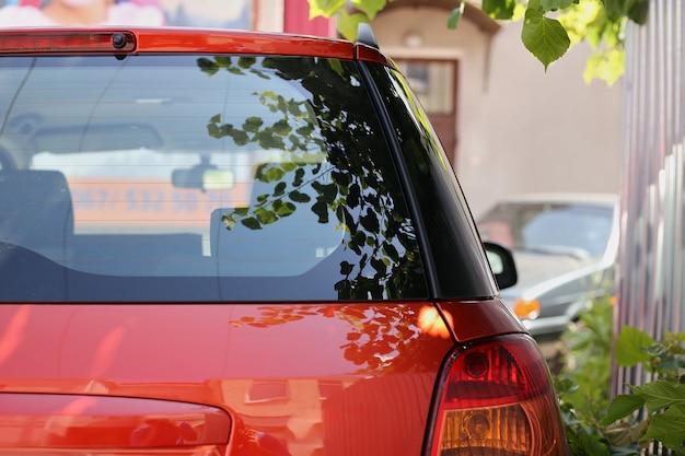 Tylny okno parkujący na ulicie w lato słonecznym dniu czerwony samochód, tylni widok. makieta naklejek lub naklejek