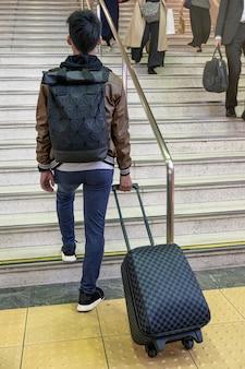 Tylny podróżnik ciągnący bagaż po szachownicy na schodach w metrze