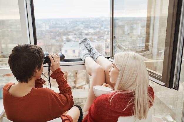 Tylny portret gorące atrakcyjne kobiety siedzi na balkonie z nogami opierał się o okno, używa lornetkę i pije kawę. kobiety wygłupiają się i szpiegują sąsiadów lub podziwiają krajobrazy miasta