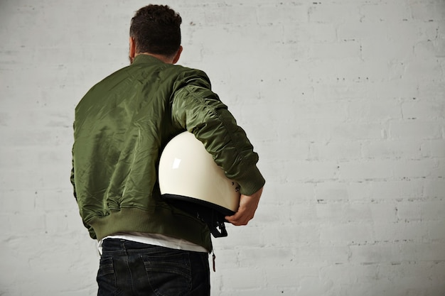 Tylny portret mężczyzny w dżinsach, krótka kurtka khaki z błyszczącym białym kaskiem motocyklowym pod pachą na białym tle