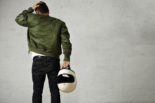 Tylny portret młodego motocyklisty w dżinsach, wojskowej kurtce bombowej i trzymającej swój biały hełm dotykając jego włosów na białym tle