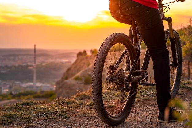 Tylny strzał rowerzysta górski przy zmierzchu obsiadaniem na bicyklu
