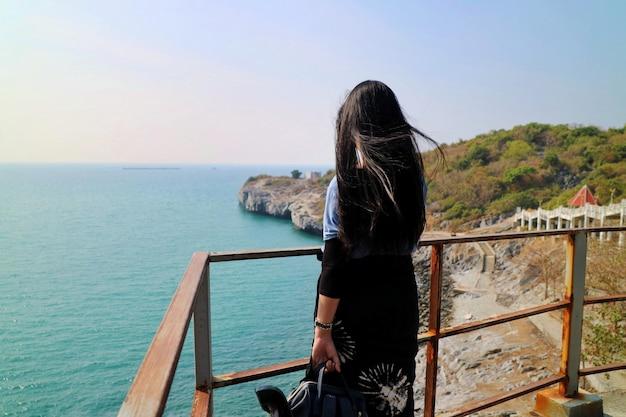 Tylny widok azjatycka kobiety pozycja przy widoku punktem i oglądać morze w lato czasie.