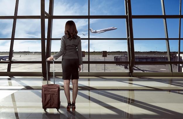 Tylny widok azjatykcia kobieta niesie walizkę na lotnisku