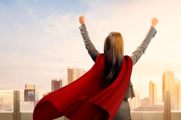Tylny widok azjatykcia super biznesowa kobieta z peleryną czuje szczęśliwy