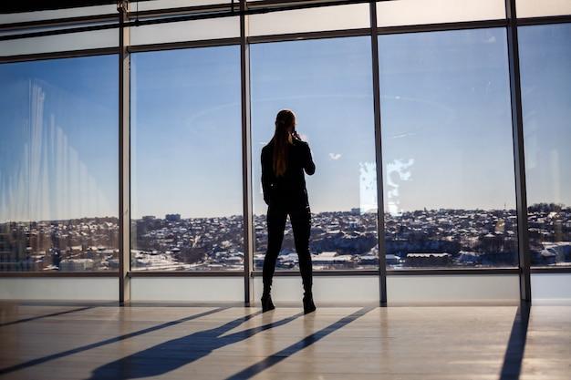 Tylny widok biznesmena patrząc przez duże okno z widokiem na miasto. w rękach trzyma telefon. widok poziomy.
