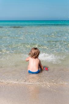 Tylny widok dzieciak siedzi przy brzeg